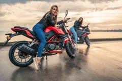 Två cyklistflickor i läderomslag på sportmotorcyklar för en svart och för röd färg arkivbilder