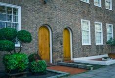 Två dörrar från kurvorna av ingången, en intressant fasad Arkivbild