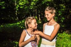 Två döttrar som kramar i parkera Arkivbild