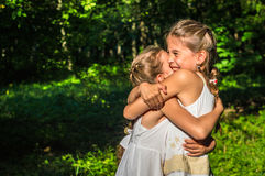 Två döttrar som kramar i parkera royaltyfri fotografi
