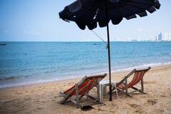 Två dagdrivare och ett paraply på det blåa havet på stranden av Pattaya, Thailand tillbaka sikt royaltyfri bild