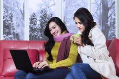 Två damer som använder bärbara datorn i vinterdag Arkivbild
