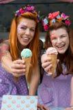 Två damer som bär blommahuvudbindlar som rymmer glass från lastbilen royaltyfri bild