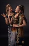 Två dansa unga kvinnor i den nationella indiska dräkten Royaltyfria Foton
