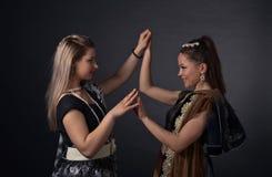Två dansa unga kvinnor i den nationella indiska dräkten Royaltyfri Bild