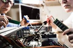 Två datortekniker som reparerar maskinvara royaltyfri bild