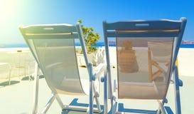 Två deckchairs på taket av byggnad på den Santorini ön, Grekland Sikt på calderaen och det Aegean havet, solig dag, blå himmel royaltyfri fotografi
