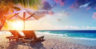 Två Deckchairs under slags solskydd i tropisk strand royaltyfri bild