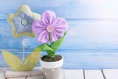 Två dekorativa blommor i kruka på blå träbakgrund Arkivfoton