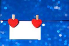 Två dekorativa röda hjärtor med hälsningkortet som hänger på blå ljus bokehbakgrund, begrepp av valentindagen Arkivfoton