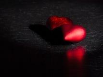 Två dekorativa röda hjärtor på svart mörkt ljus och på den wood tabellen, begrepp av valentindagen arkivbild