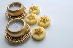 Två dekorativa stearinljus i guld- färg och fyra stearinljus med stjärnamodellen Royaltyfri Bild