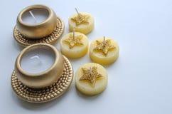 Två dekorativa stearinljus i guld- färg och fyra stearinljus med stjärnamodellen Arkivbilder