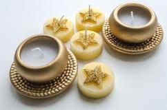 Två dekorativa stearinljus i guld- färg och fyra stearinljus med stjärnamodellen Royaltyfri Fotografi