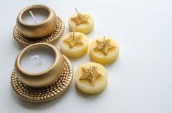 Två dekorativa stearinljus i guld- färg och fyra stearinljus med stjärnamodellen Arkivfoto