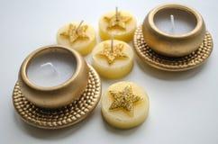 Två dekorativa stearinljus i guld- färg och fyra stearinljus med stjärnamodellen Royaltyfri Foto