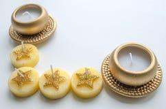 Två dekorativa stearinljus i guld- färg och fyra stearinljus med stjärnamodellen Fotografering för Bildbyråer