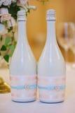 Två dekorerade flaskor av champagne på bröllopberömmen Arkivbilder