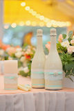 Två dekorerade flaskor av champagne på bröllopberömmen Royaltyfria Bilder
