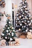 Två dekorerade julgranen med gåvaasken nära klassisk firepl Royaltyfria Bilder