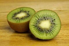 Två del av kiwi på trä bordlägger Fotografering för Bildbyråer