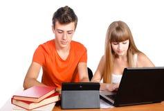Två deltagare som lärer med böcker och bärbar dator Arkivfoton