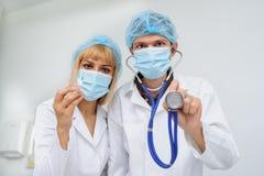 Två doktorer med mascken, stetoskopet i hand och injektionen royaltyfri foto
