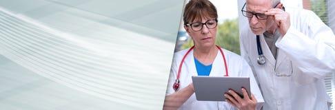 Två doktorer som diskuterar om medicinsk rapport på minnestavlan panorama- baner royaltyfri foto