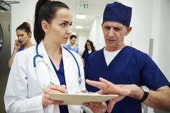 Två doktorer som diskuterar sjukdomshistorier i korridoren royaltyfri foto