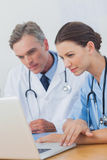 Två doktorer som fokuseras på en bärbar datorskärm Arkivbild