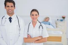 Två doktorer som framme står av en lagd in på sjukhus tålmodig Fotografering för Bildbyråer