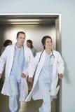 Två doktorer som kör ut ur hissen Arkivfoto