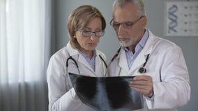 Två doktorer som kontrollerar lungaröntgenstrålen och att ha diskussion på diagnosen, pulmonology lager videofilmer