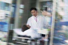 Två doktorer som rullar i en patient på en bår till och med dörrarna av sjukhuset arkivbilder