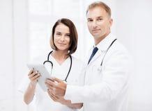 Två doktorer som ser minnestavlaPC royaltyfri fotografi
