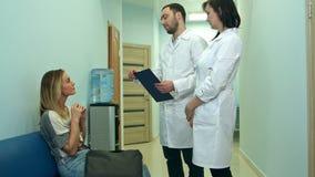 Två doktorer som talar till ett kvinnligt tålmodigt sammanträde i sjukhuskorridoren stock video