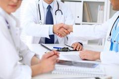 Två doktorer som till varandra som skakar händer sitter på tabellen i sjukhuskontor Royaltyfria Bilder