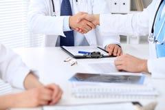 Två doktorer som till varandra som skakar händer sitter på tabellen i sjukhuskontor Royaltyfri Bild