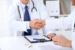 Två doktorer som till varandra som skakar händer sitter på tabellen i sjukhuskontor Royaltyfri Foto