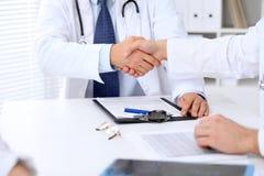 Två doktorer som till varandra som skakar händer sitter på tabellen i sjukhuskontor Royaltyfri Fotografi