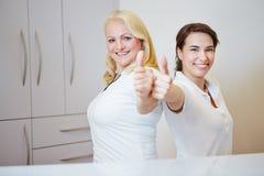 Två doktorsassistenter som rymmer upp tummar Arkivbild