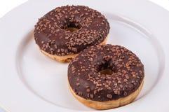 Två donuts med chololateglasyr på den vita plattan Arkivfoton