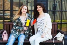 Två dräkter för mode för flickaflickvänner iklädda vilar, äter glass eskimo Royaltyfria Bilder