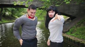 Två driftiga män fejkar in muskeldräkter dansar, i att sväva den närliggande bron för fartyget arkivfilmer