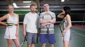 Två dubblettlag efter tennismatchen Två manliga spelare och två kvinnliga spelare Dem som tillsammans står och att le och arkivfilmer