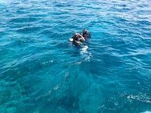 Två dykare i vattentäta dräkter för svart dykning med aluminum kanistrar för skinande metall svävar, fördjupar i blått havsvatten royaltyfri bild