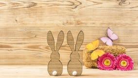 Två easter kaniner med blommor och fjärilar Arkivfoto