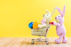 Två easter kaniner med shoppingvagnen och easter ägg Arkivfoto