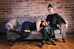 Två eleganta latinska kvinnadansare i svarta klänningar som poserar nära soffan Royaltyfria Foton