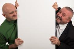 Två eleganta män som ler efter en tom panel på vit bakgrund Royaltyfria Bilder